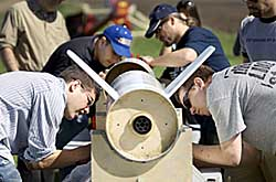Students bending over, working on a rocket lying in a horizontal bracket
