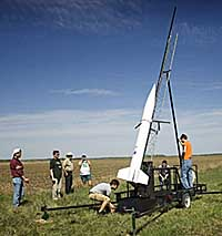 Students standing in a field with a rocket angled on a launch stand