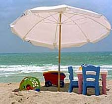 A large umbrella casts a shadow on toys on the beach