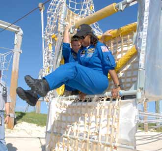 Mission Specialist Stephanie Wilson practices jumping out of an escape basket at the launch pad.