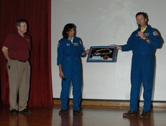 Michael Lopez-Alegria and Sunita Williams make a presentation to Kennedy Space Center's Michael Wetmore.