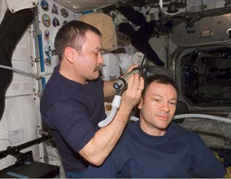 Michael Lopez-Alegria gets a haircut aboard the International Space Station.