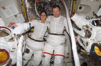 Astronauts Michael Lopez-Alegria and Sunita Williams prepare for a spacewalk.