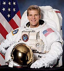 Scott Parazynski wearing a white extravehicular activity suit