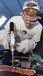 Scott Parazynski, with safety glasses over his eyes, a baseball cap backwards on his head and white spacewalk gloves, uses a drill-like tool