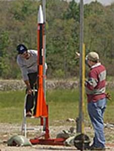 Two students examine a rocket on a launch pad