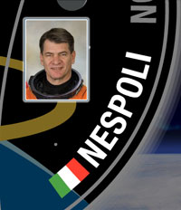 A close-up view of the name Nespoli on the STS-120 mission patch and a photo of Paolo Nespoli