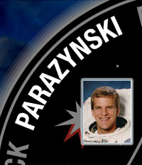 A close-up view of the name Parazynski on the STS-120 mission patch and a photo of Scott Parazynski