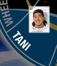A close-up view of the name Tani on the STS-120 mission patch and a photo of Daniel Tani