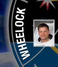 A close-up view of the name Wheelock on the STS-120 mission patch and a photo of Doug Wheelock
