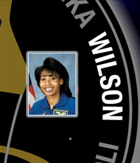 A close-up view of the name Wilson on the STS-120 mission patch and a photo of Stephanie Wilson