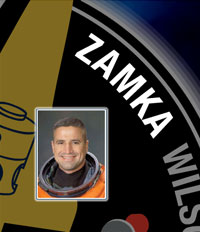 A close-up view of the name Zamka on the STS-120 mission patch and a photo of George Zamka