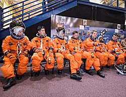 The seven crew members sit in training versions of their orange launch and entry spacesuits