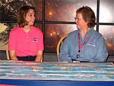 Rachel Manzer and Susan Moore sit behind a table with a world map on it