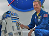 Astronaut Jim Reilly with R2-D2 and the Star Wars lightsaber.