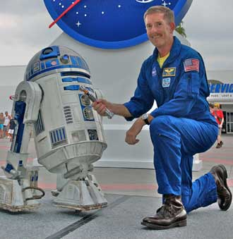 Astronaut Jim Reilly with R2-D2 and a lightsaber from Star Wars.