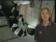 A girl stands in front of a picture of an astronaut floating inside the International Space Station