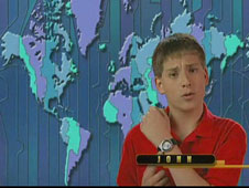 A boy points to his wristwatch as he stands in front of a world map that is divided into time zones