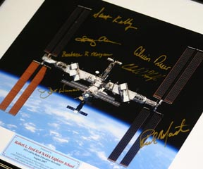 Crew signatures surround a picture of the space station