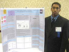 Kevin Jagdipsingh stands beside his poster