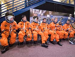 The seven crewmembers sit in training versions of their orange launch and entry spacesuits