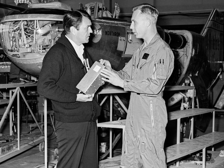 NASA engineer and test pilot Bruce Peterson (right) discusses the M2-F2 Lifting Body airplane with actor James Doohan