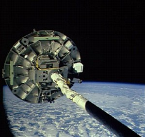 Wake Shield Facility being held out in space by the shuttle's robot arm