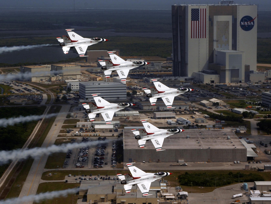 U.S. Air Force Thunderbird F-16 jets fly in formation past the Vehicle Assembly Building at the Kennedy Space Center