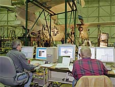 Two men sit at computers while testing an airplane in the background