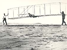 Historic photo of the Wrights' third test glider being launched, with one man aboard and one to each side of the glider