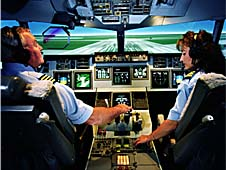 Two pilots sit at the controls of an airplane simulator