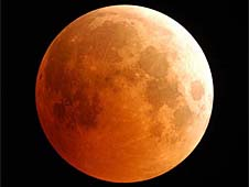 A reddish-orange picture of our moon during a total lunar eclipse