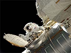 An astronaut can be seen in the open airlock of the International Space Station as he gets ready to close the hatch