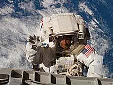 An astronaut dressed in a large, bulky spacesuit waves to the camera while working in space