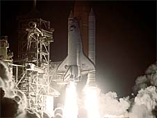 Against a black night sky, the space shuttle Discovery and its seven-member crew head toward Earth orbit