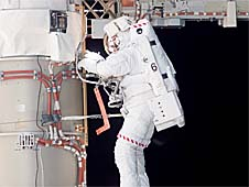 Steven Swanson completes a spacewalk outside the International Space Station while wearing a spacesuit