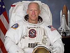 Astronaut Patrick Forrester poses for a picture in a white spacesuit