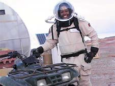 LaTasha Taylor wearing a spacesuit and standing next to an all-terrain vehicle