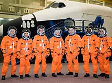 The seven crew members stand in front of a space shuttle trainer