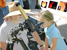 A woman stands next to a girl looking through a telescope
