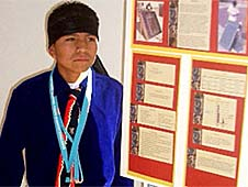 Garrett Yazzie, dressed in traditional Navajo clothing, standing beside a poster about his project