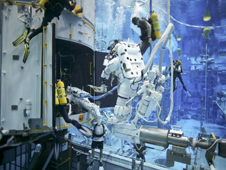 SCUBA divers assisting astronauts during training underwater