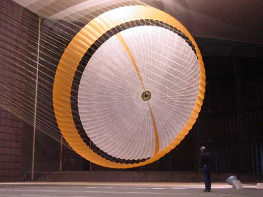 engineer dwarfed by parachute being tested for landing system for Mars Science Laboratory