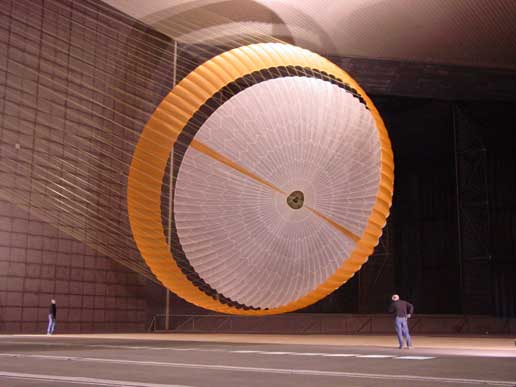 two engineers are dwarfed by parachute being tested as part of Mars Science Laboratory landing system