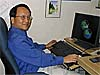 NASA scientist Lee-Lueng Fu smiles while sitting at his computer studying satellite images