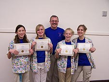 Four girls stand with their teacher and hold their award certificates