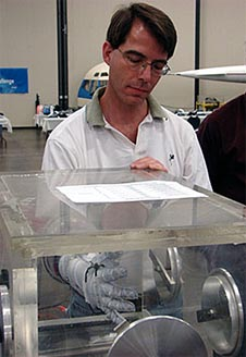 Peter Homer using a white pressurized glove in a clear glove box
