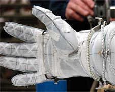 A white astronaut glove with a white ribbon 'X' on each finger joint