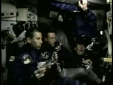 Astronauts float while they eat breakfast in the space shuttle