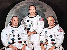 Apollo 11 astronauts in their spacesuits in front of an image of the moon